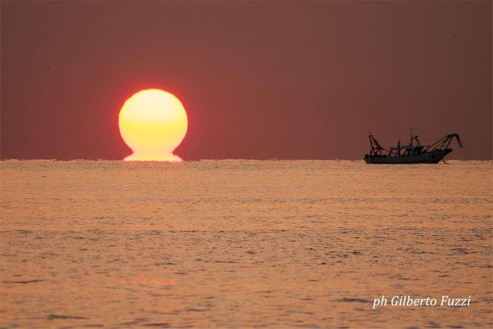Sorgere del sole e peschereccio